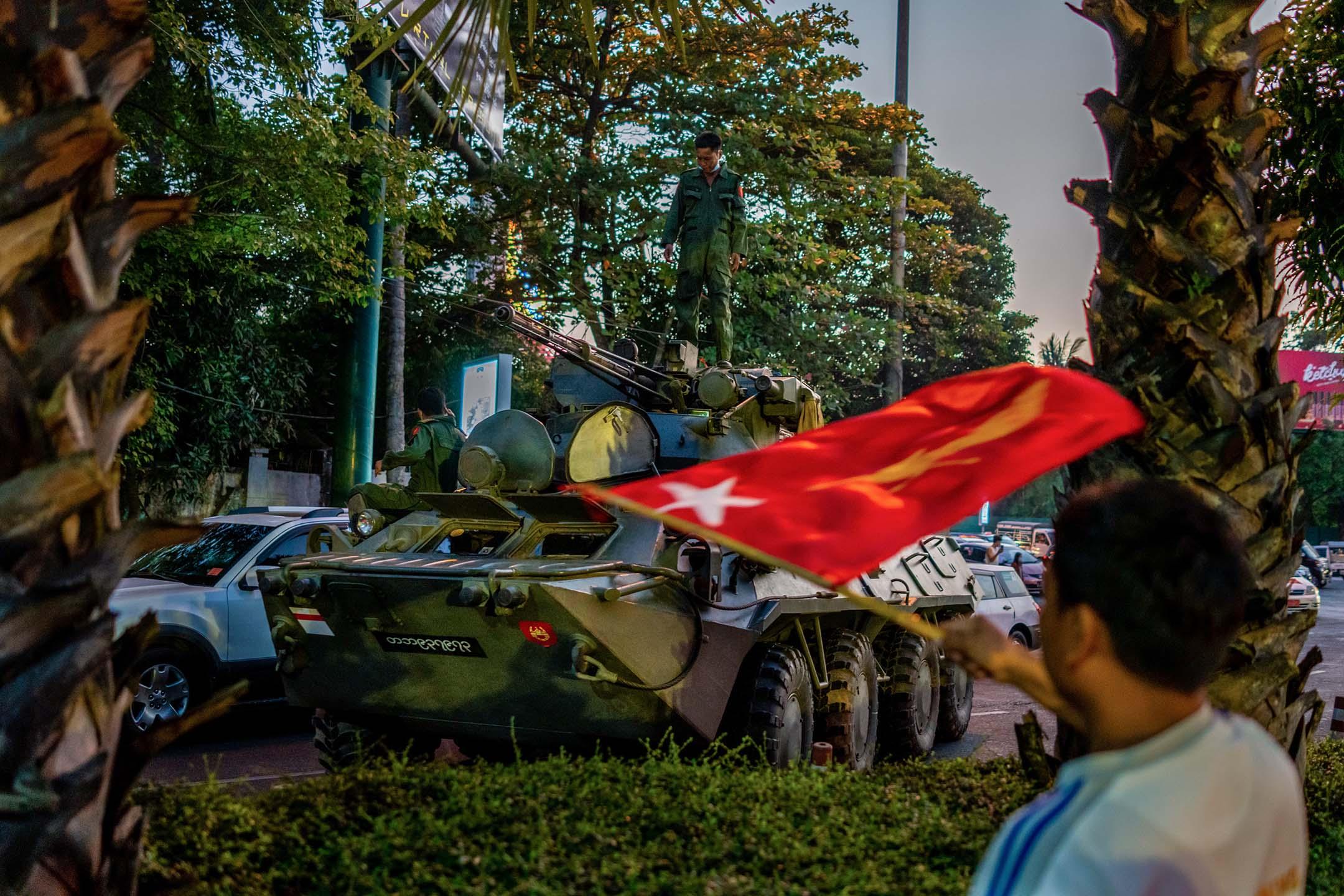 2021年2月14日緬甸仰光,市民在一輛裝甲車附近揮動全國民主聯盟的旗幟。