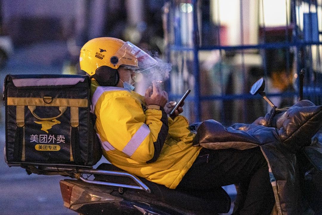 2020年2月1日,一名美團外賣送貨員在街道上休息。 攝:Artyom Ivanov\TASS via Getty Images