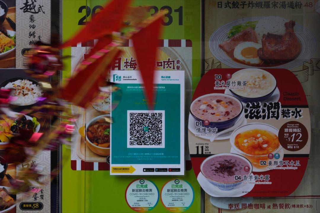 2021年2月17日,香港,商戶按政府要求在店外貼上「安心出行」二維碼。 攝:林振東/端傳媒