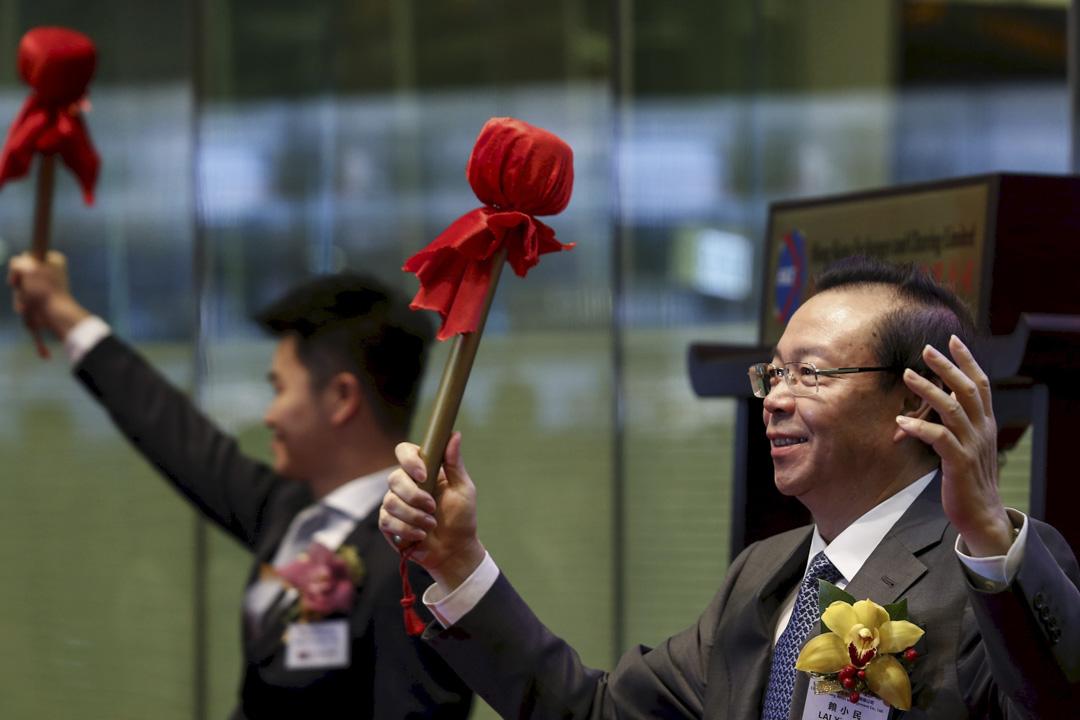 2015年10月30日,中國華融資產管理公司在香港交易所上市,董事長賴小民在現場表現興𡚒。