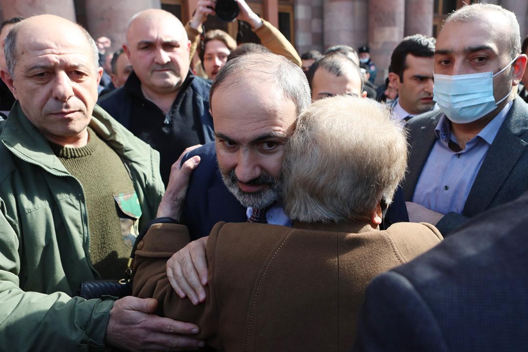 2021年2月25日在亞美尼亞首都耶烈萬,總理帕希尼揚(Nikol Pashinyan)與一名支持者擁抱。 攝:Hayk Baghdasaryan / TASS via Getty Images
