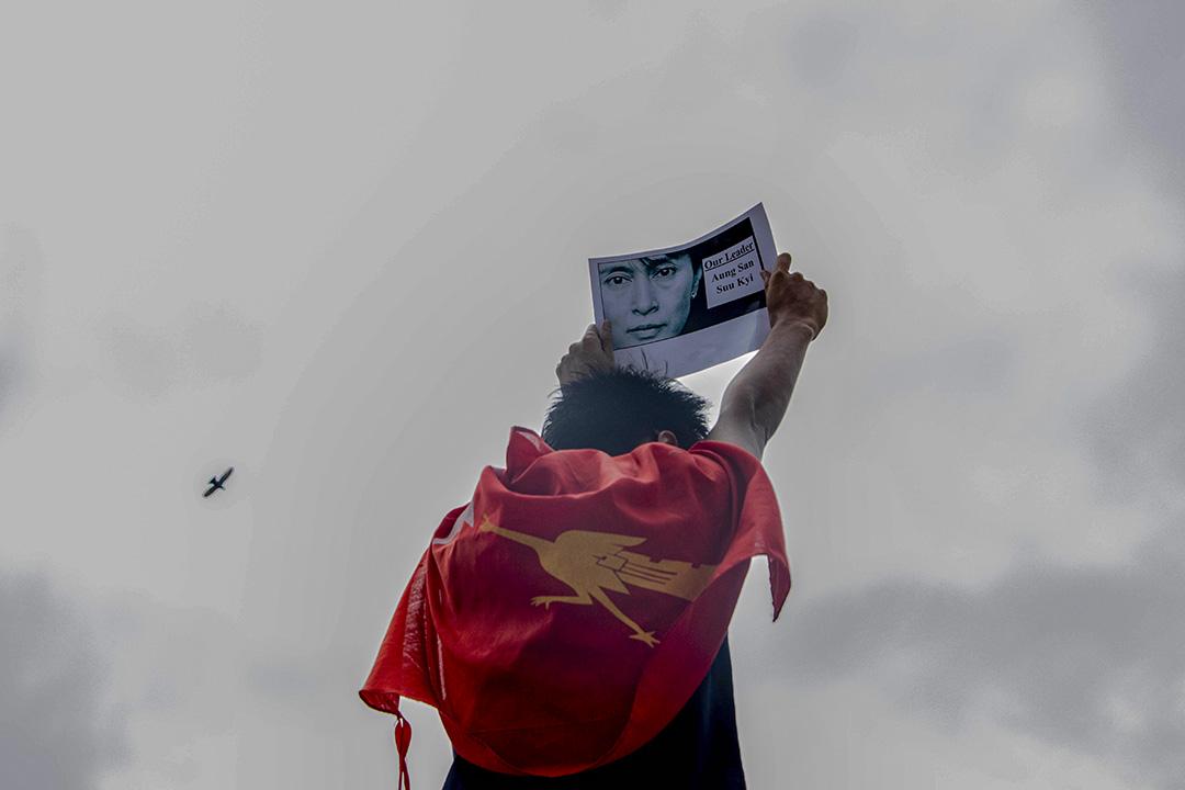 2021年2月8日緬甸,示威者在示威期間舉著標語牌上面貼有昂山素姬的畫像,並披上全緬學生會的旗幟。