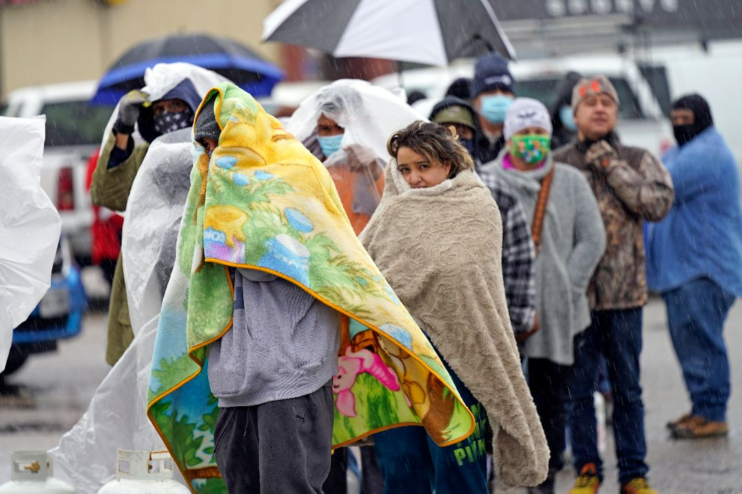2021年2月17日,美國德州侯斯頓,寒冷風暴致大面積停電,居民排隊領天然氣罐取暖。 攝:David J. Phillip/AP Photo