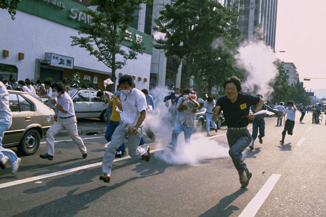 1987年6月26日,首爾街頭的示威遊行,學生抗議者在催淚彈中奔跑。