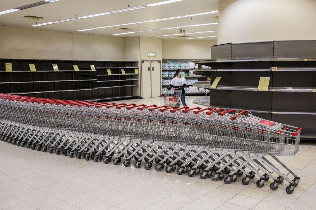 2020年2月7日,香港西環寶翠園超市的日用品被搶購一空,已購買一包米的市民在貨架之間。 攝:林振東/端傳媒