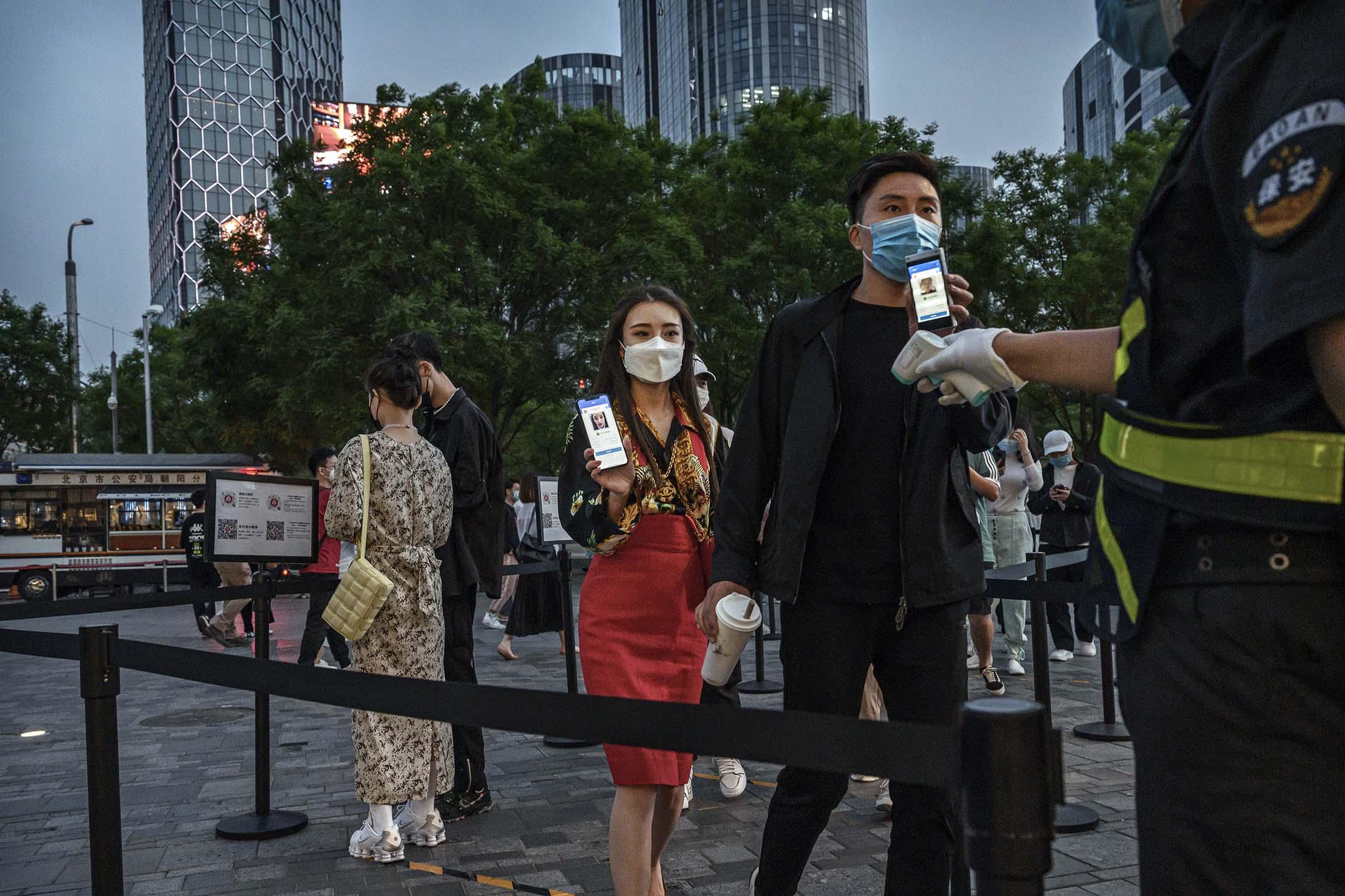 2020年5月3日北京,一名中國男人和婦女在假期期間,於進入購物中心前,一名警衛查看他們的健康碼。