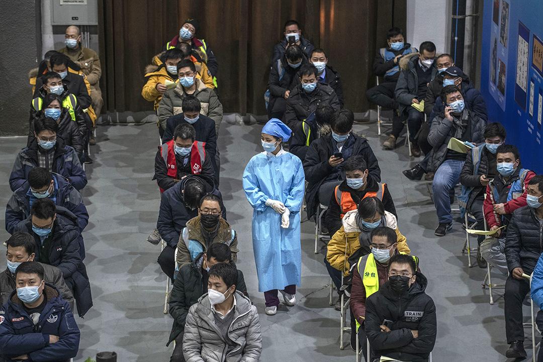 2021年1月15日中國北京,工人包括保安人員,在朝陽區的疫苗接種中心等待接種疫苗。