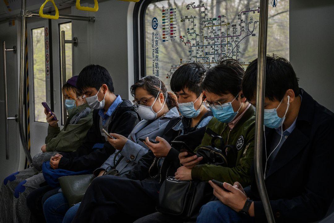 2020年4月15日,中國北京,人們坐在地鐵上看手機。 攝:Kevin Frayer/Getty Images