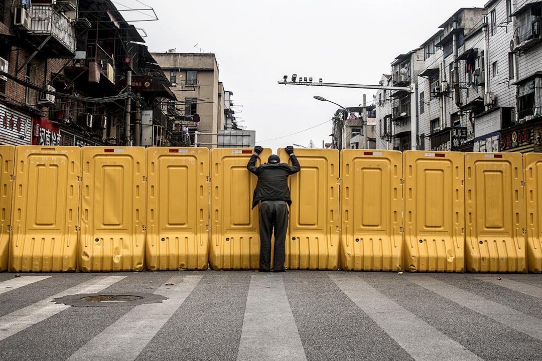 2020年3月8日,封城中的武漢,一個戴著口罩的男士隔著圍板與住宅區內的人交談。