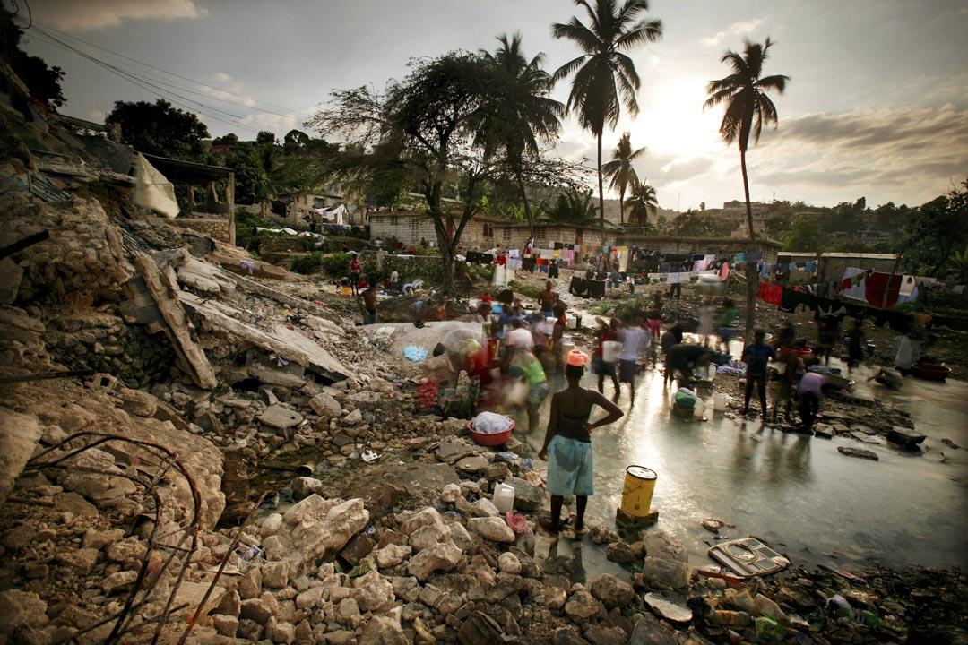 2010年2月9日,海地地震倖存者在被毀的房屋旁小溪洗衣服。 攝:Mario Tama/Getty Images