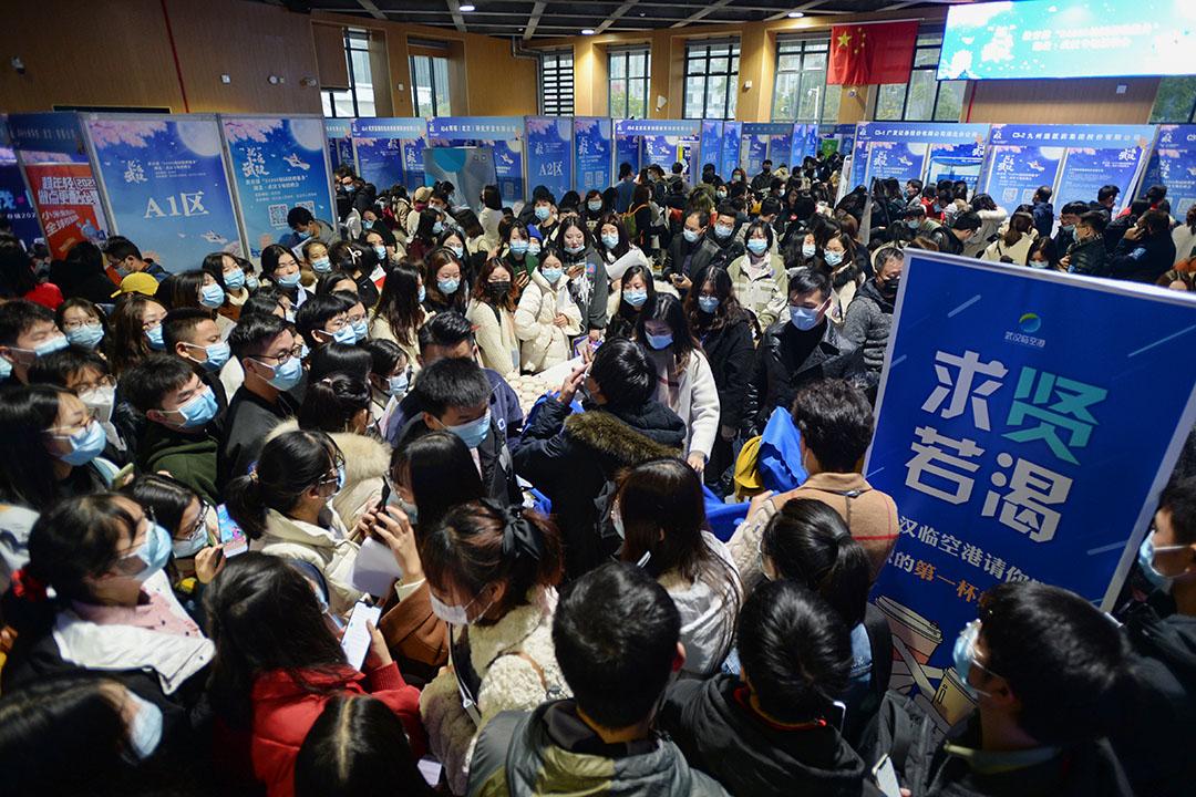 2020年12月2日中國武漢,戴著口罩的畢業生於湖北省武漢市的體育館參加招聘會。