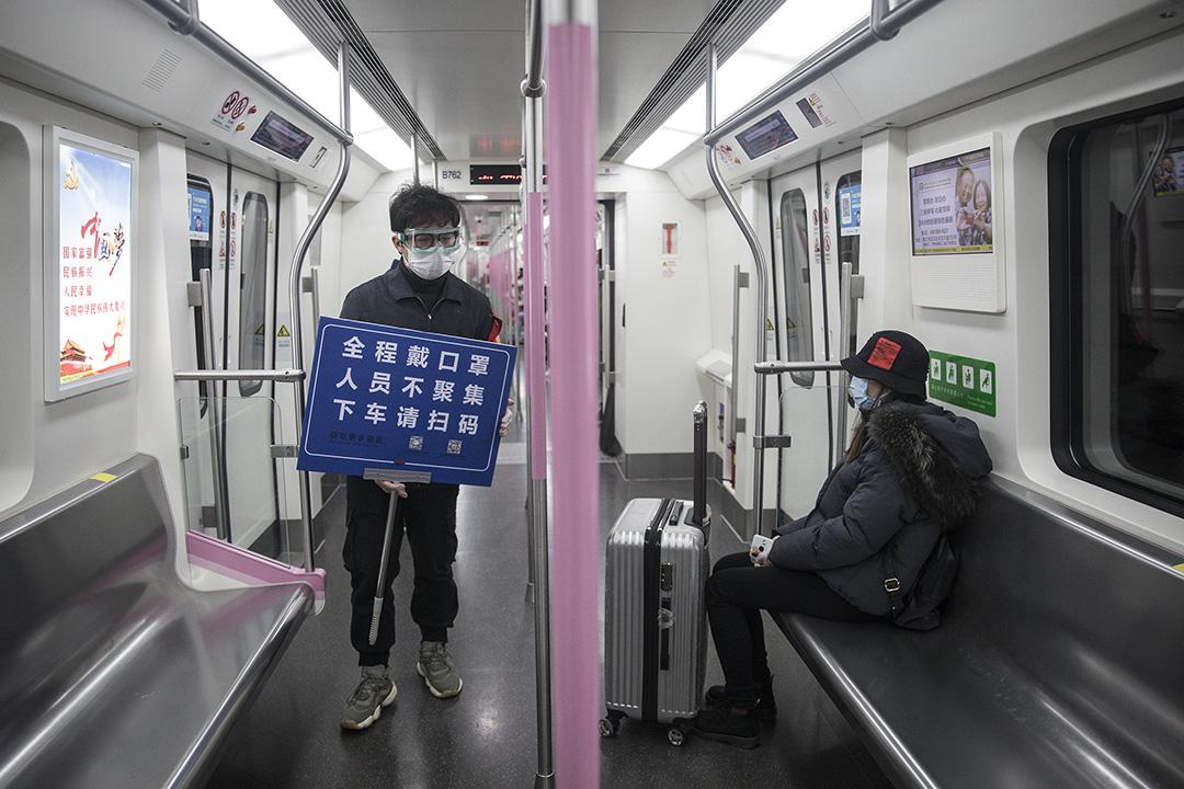 2020年3月28日武漢,地鐵工作人員舉起紙牌提醒乘客戴口罩,及掃描健康碼。