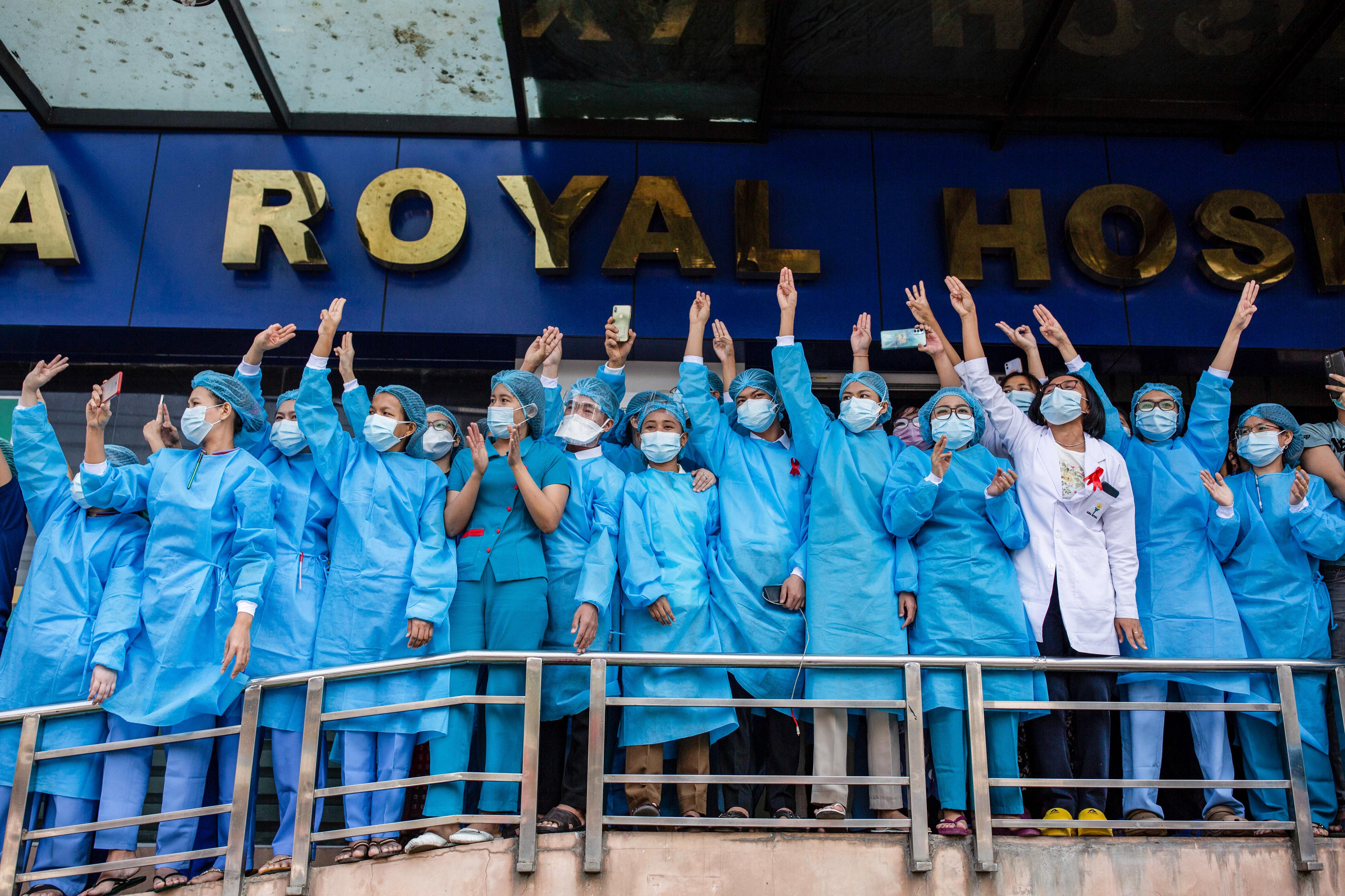 2021年2月7年緬甸仰光,醫護工作者在反對軍政府的示威遊行中舉起三隻手指致敬。