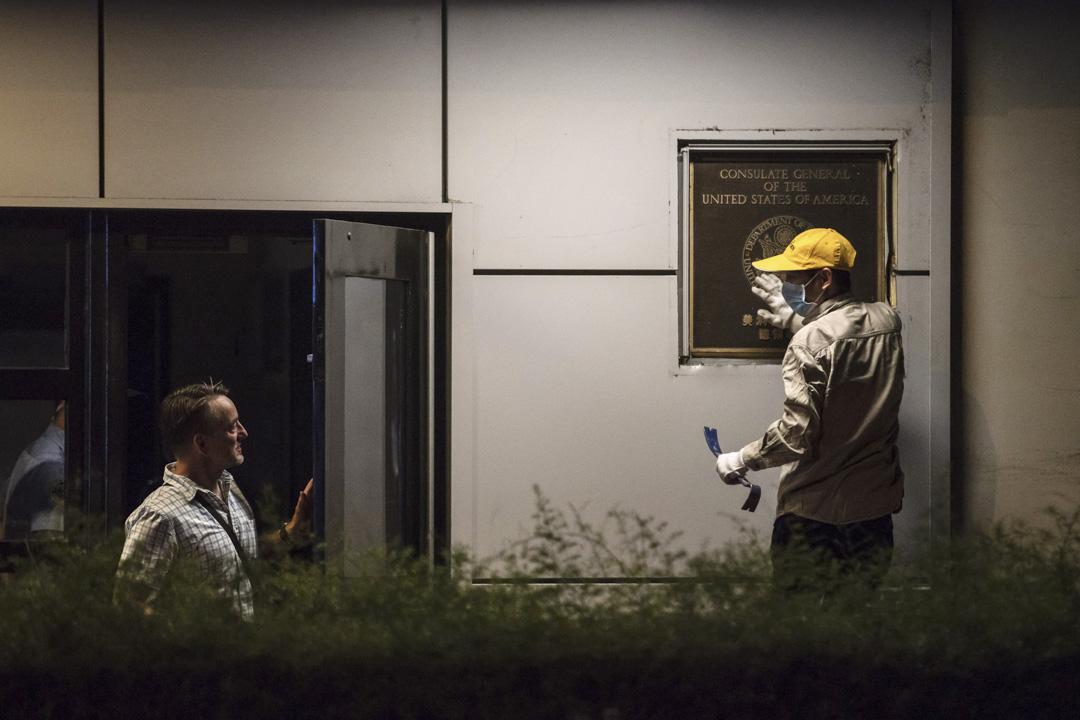 2020年7月26日晚上,美國駐成都總領事林傑偉(Jim Mullinax)與一名工人交談,工人正在清潔領事館門前的徽標。