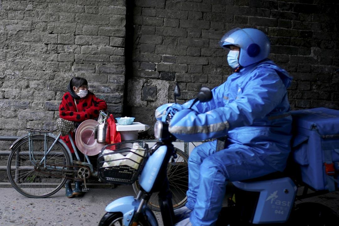 2020年3月27日,荊州一名外賣員駕車在商販前經過。 攝:Aly Song/Reuters/達志影像