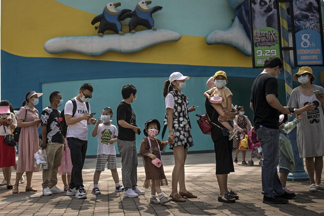 2020年6月1日武漢,訪客排隊進入公園前,工作人員檢查他們的溫度和健康碼。