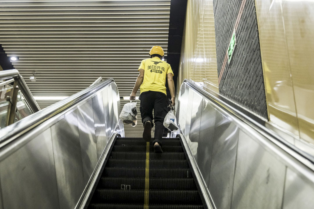 2019年8月17日,上海美團快遞員乘坐自動扶梯送食物。