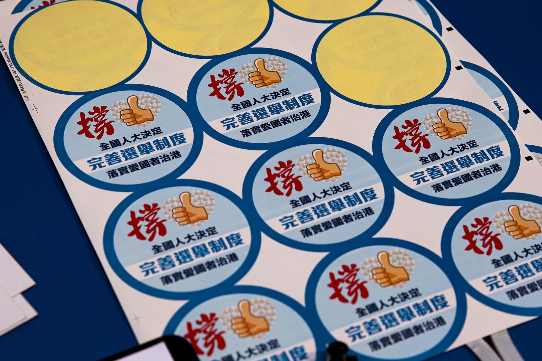 2021年3月12日灣仔,一個支持香港選舉改制的街站上,一堆派發給市民的貼紙。