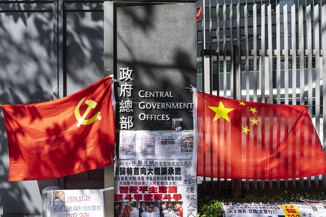 2020年11月25日在香港,一名中港政府的支持者在香港政府總部外,掛起中國國旗、中共黨旗,以至一些標語及剪報。 攝:Miguel Candela / Anadolu Agency via Getty Images