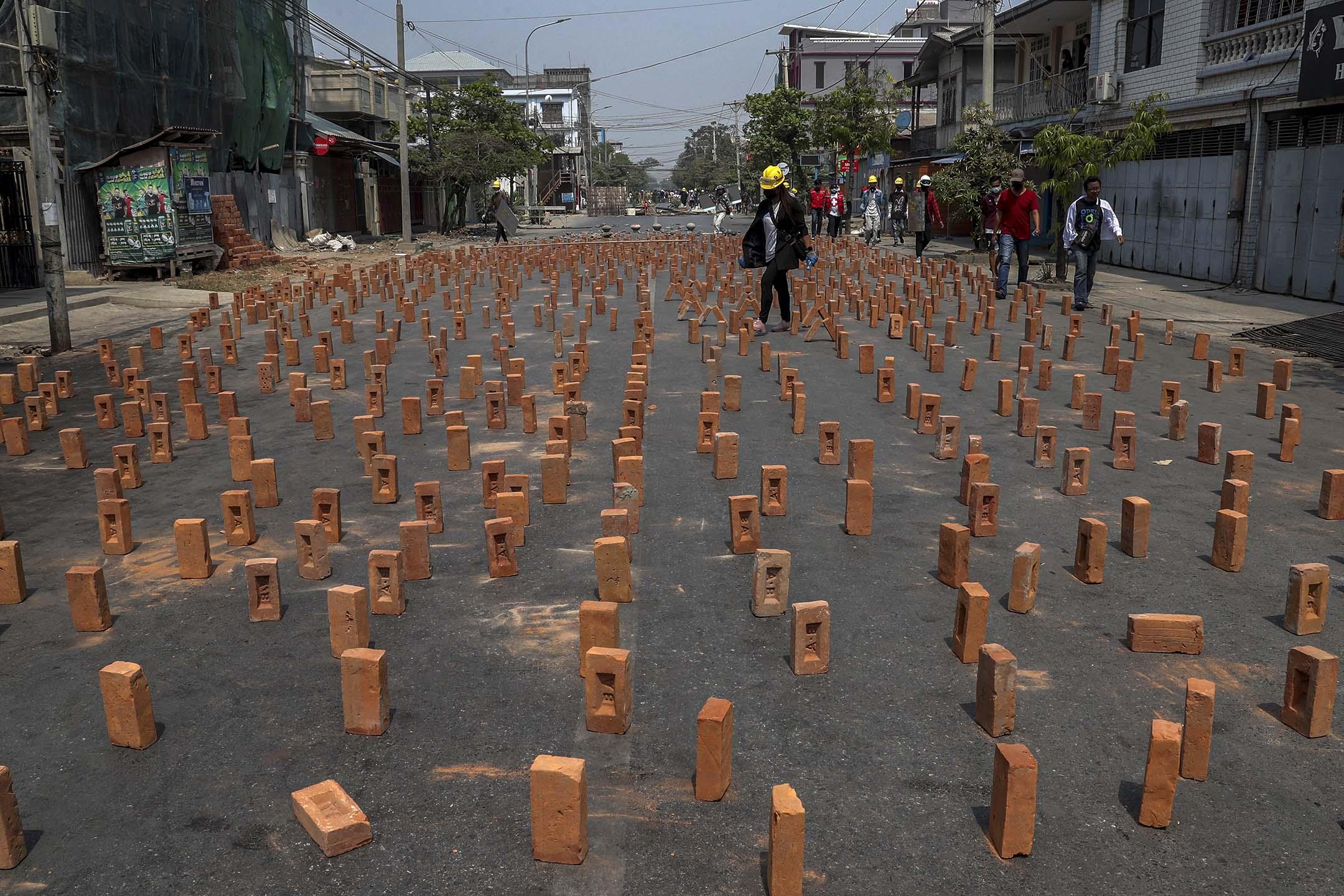 2021年3月10日緬甸曼德勒,一名示威者在道路上砌磚。