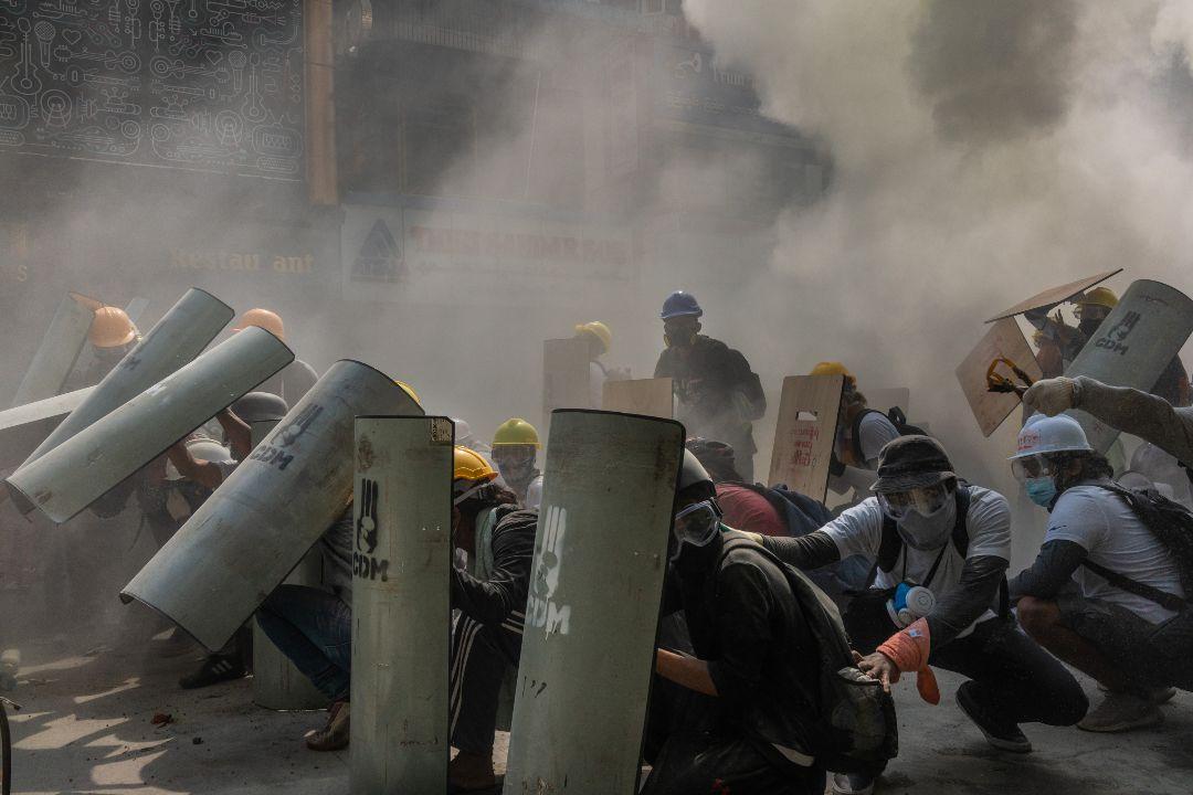 2021年2月28日,緬甸仰光,抗議者用盾牌抵抗警察發射催淚彈。 攝:Hkun Lat/Getty Images