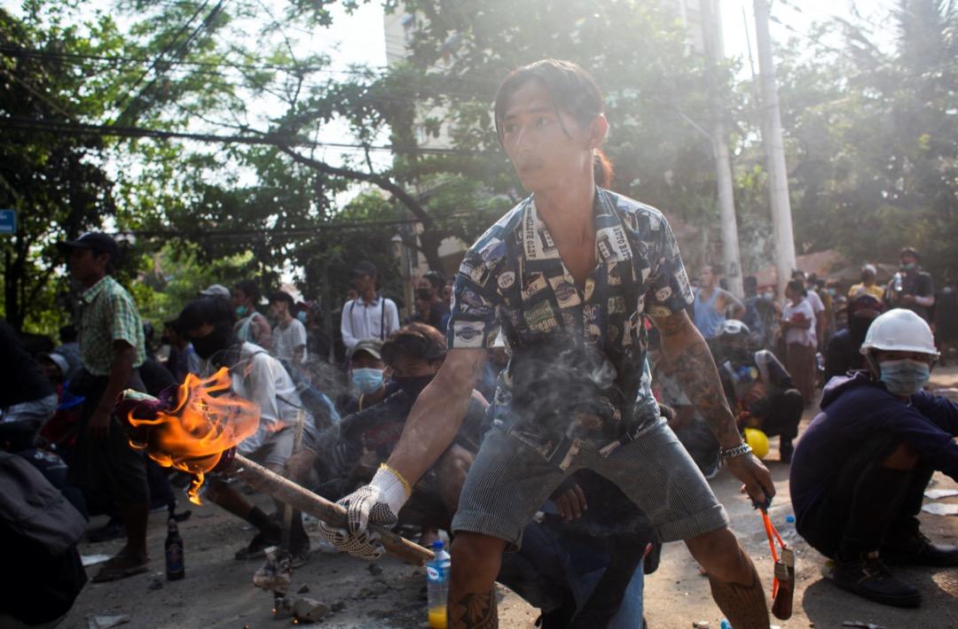 2021年3月28日,緬甸仰光,一名反軍政府示威者手持火炬。