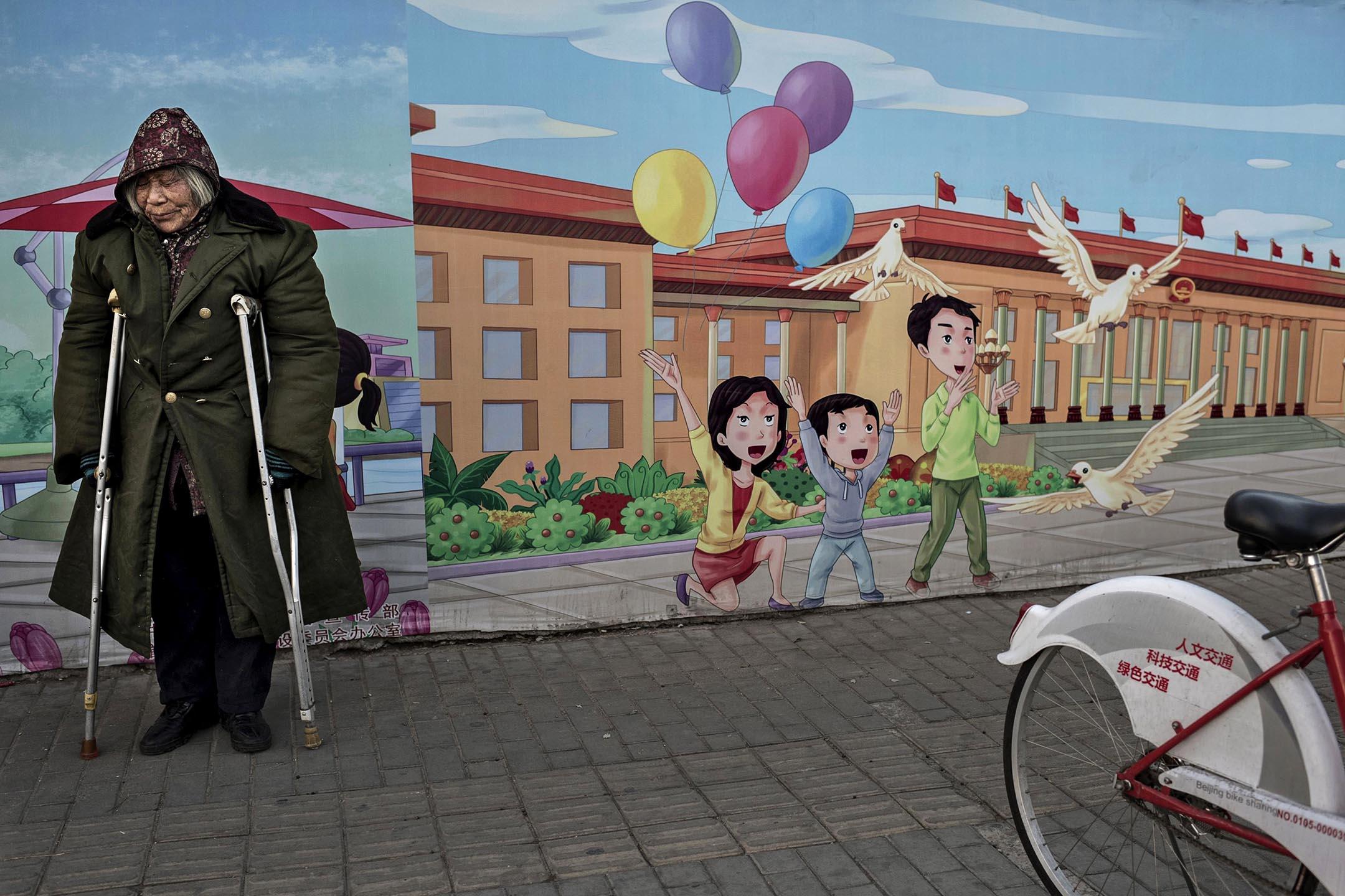 2014年12月1日北京,一位殘疾老人在街道站立在政府的宣傳廣告牌旁。