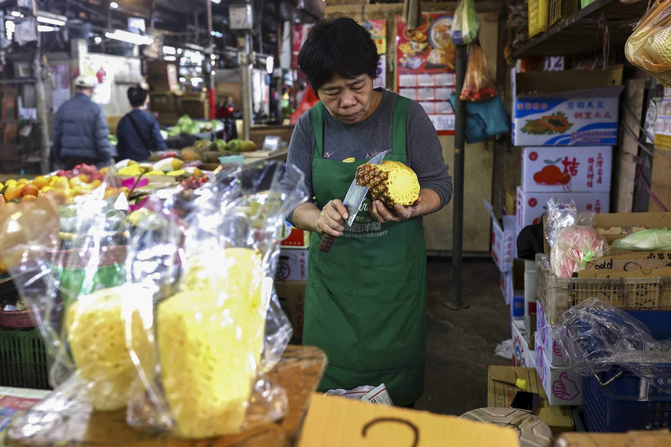 2021年3月5日,台北市的一個水果攤上,商販在準備鳳梨  。