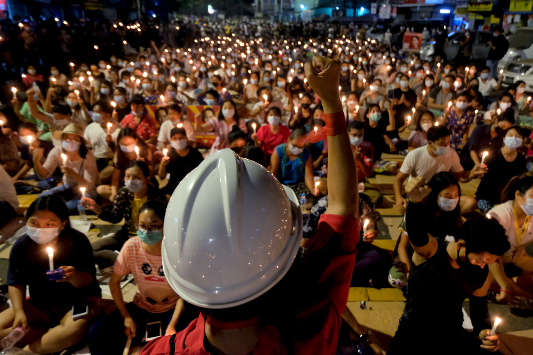 2021年3月14日,緬甸仰光燭光集會上,一名示威者用握緊的拳頭在人群面前舉起。