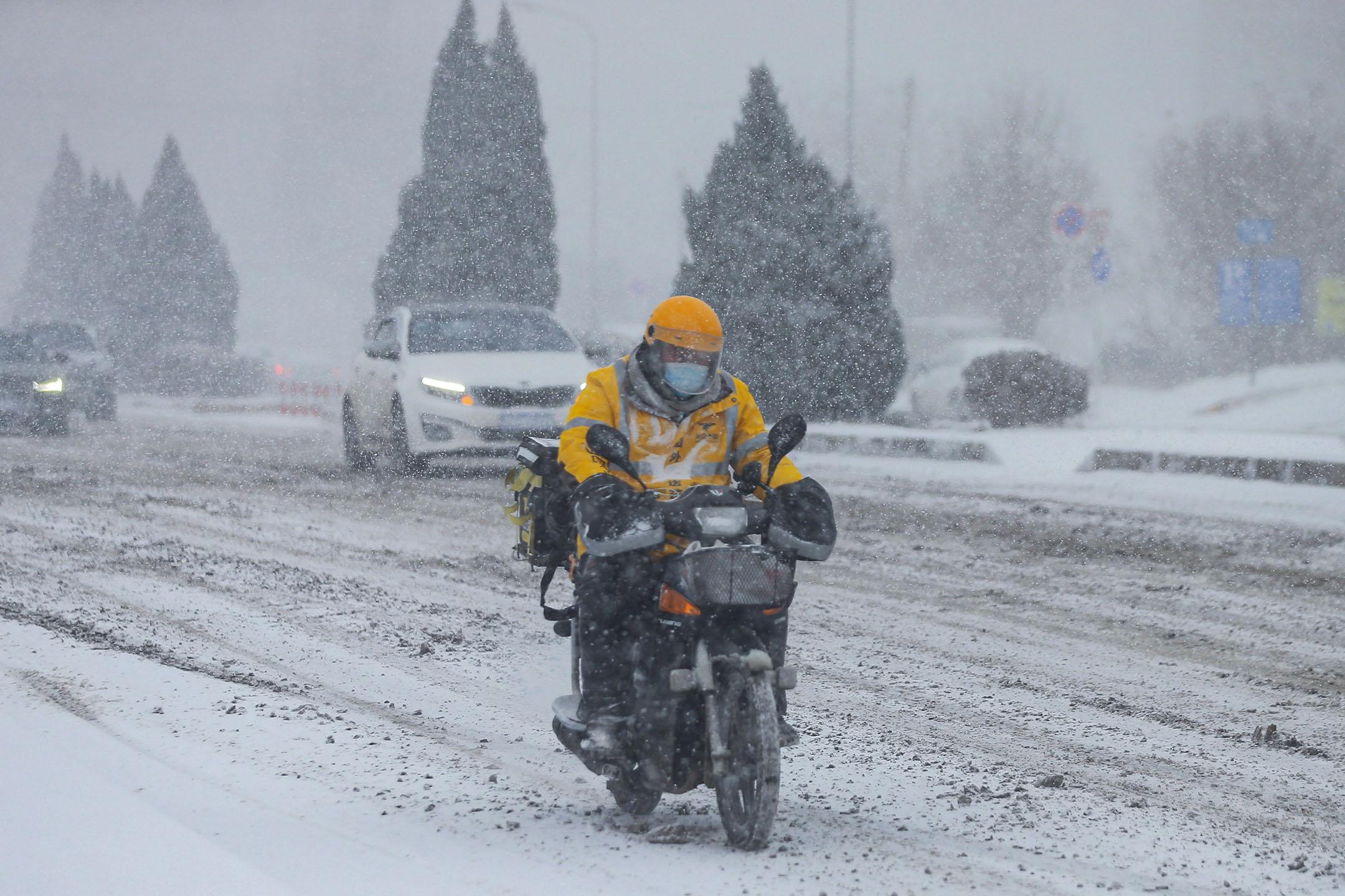 2021年1月6日中國大連,外賣騎手在暴風雪期間工作。