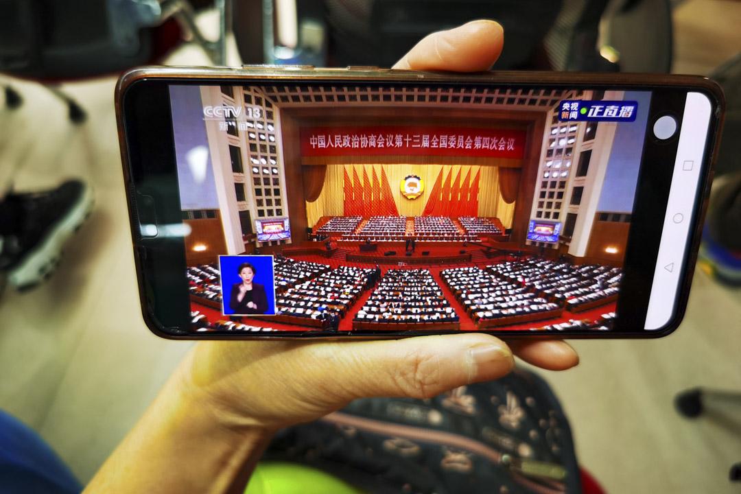 2021年3月4日,一位市民用手機觀看政協會開幕式的現場直播。 攝:Zhang Jusheng/VCG via Getty Images