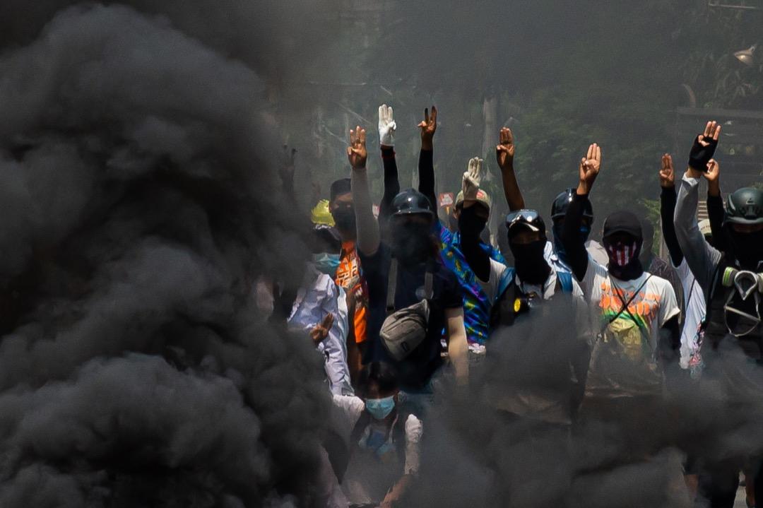 2021年3月27日,緬甸反軍政府示威持續,最大城市仰光,有示威者焚燒車胎堵路,並舉起三指手勢以示抗議。