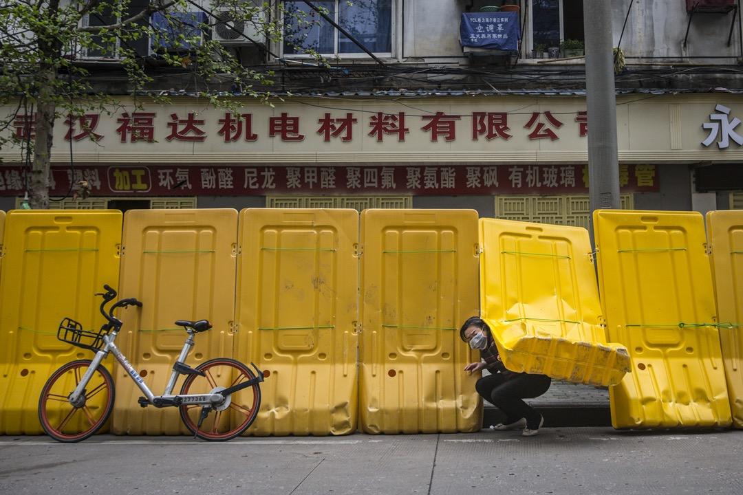 2020年3月,武漢,一名婦人在膠板罅隙中爬出來。