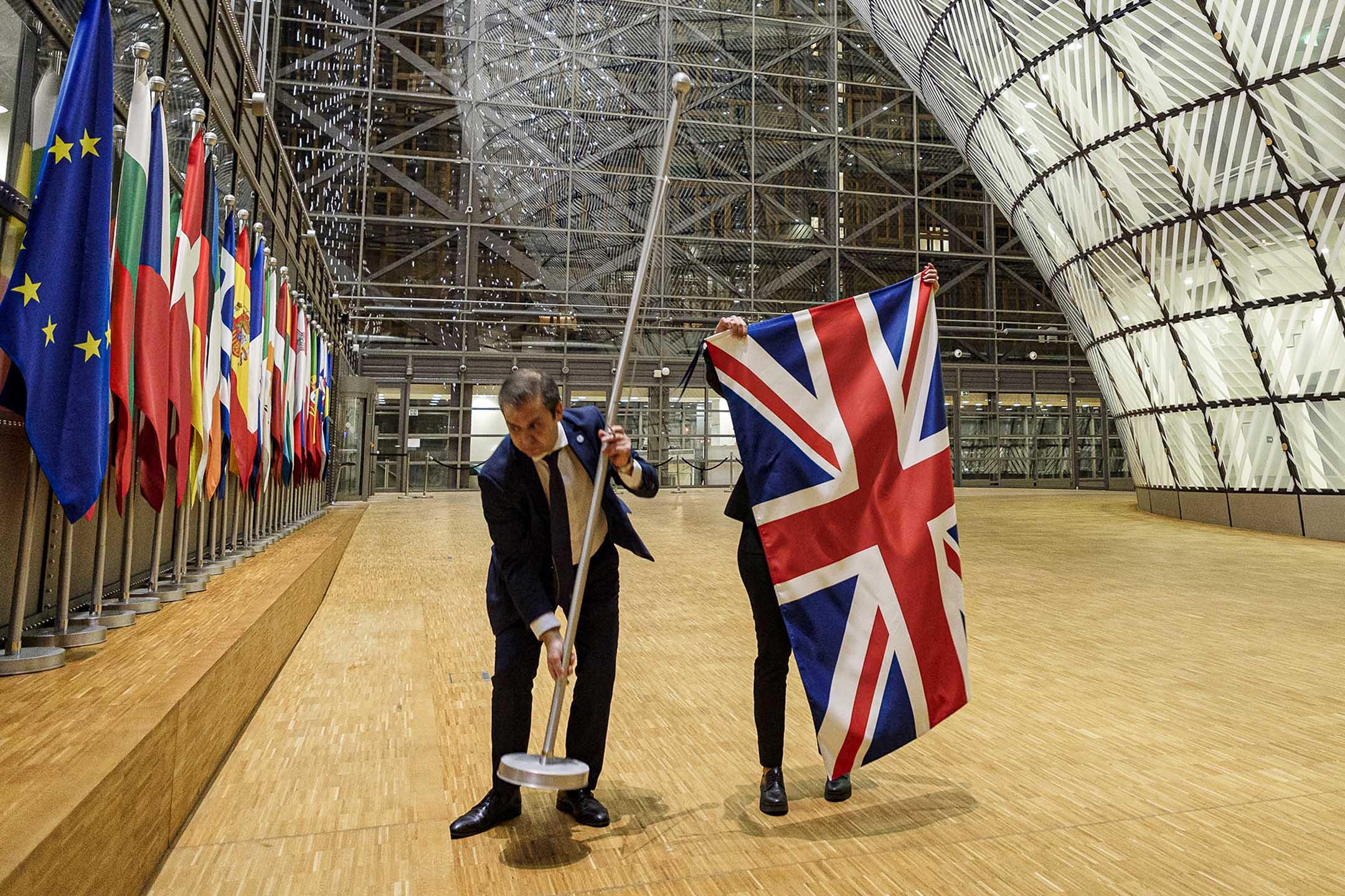 2020年1月31日比利時布魯塞爾,兩名歐盟官員在歐盟總部的中庭去除英國國旗。