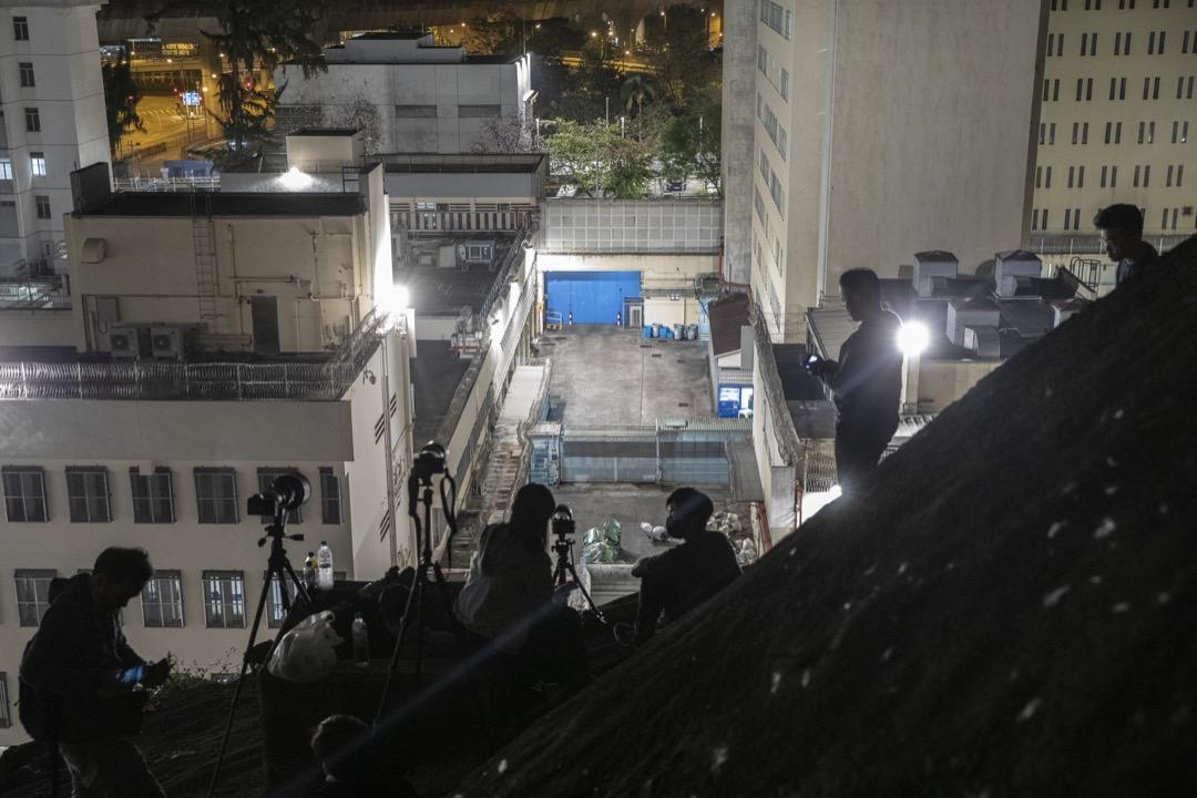 2021年3月2日凌晨,一眾攝影記者在山坡上等候拍攝被押解到荔枝角收押所的被告。