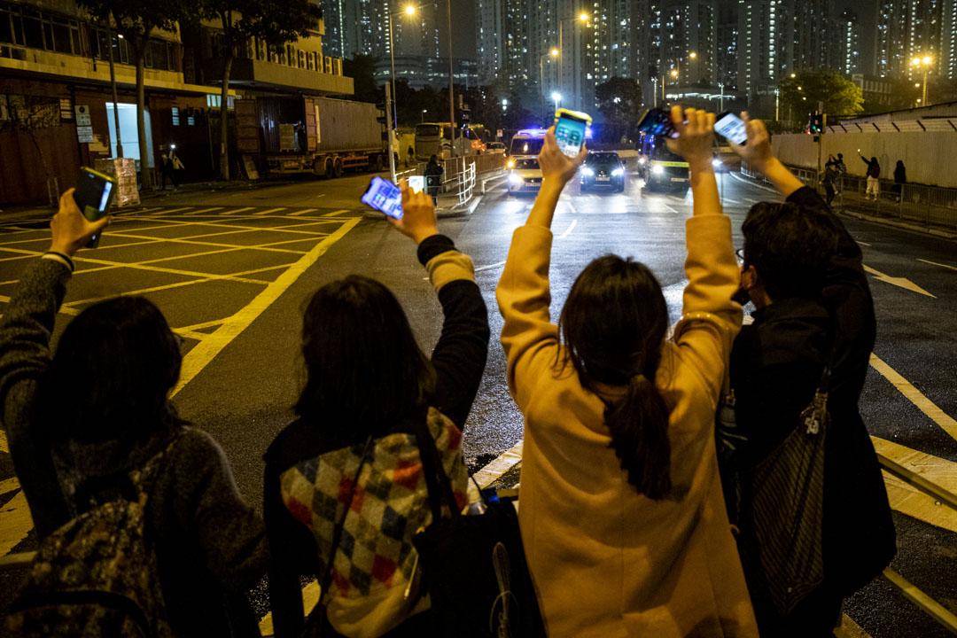 2021年3月4日,晚上十時半左右,一輛囚車由西九法院駛經荔枝角道,數十名送車市民由昇悅居對出跑出荔枝角道,並亮起手機燈向囚車送行。 攝:林振東/端傳媒