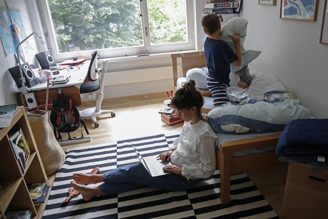 2020年8月,瑞士首都伯恩,一名女子在房間裏工作,小孩在床上玩耍。 攝:Stefan Wermuth/Bloomberg via Getty Images