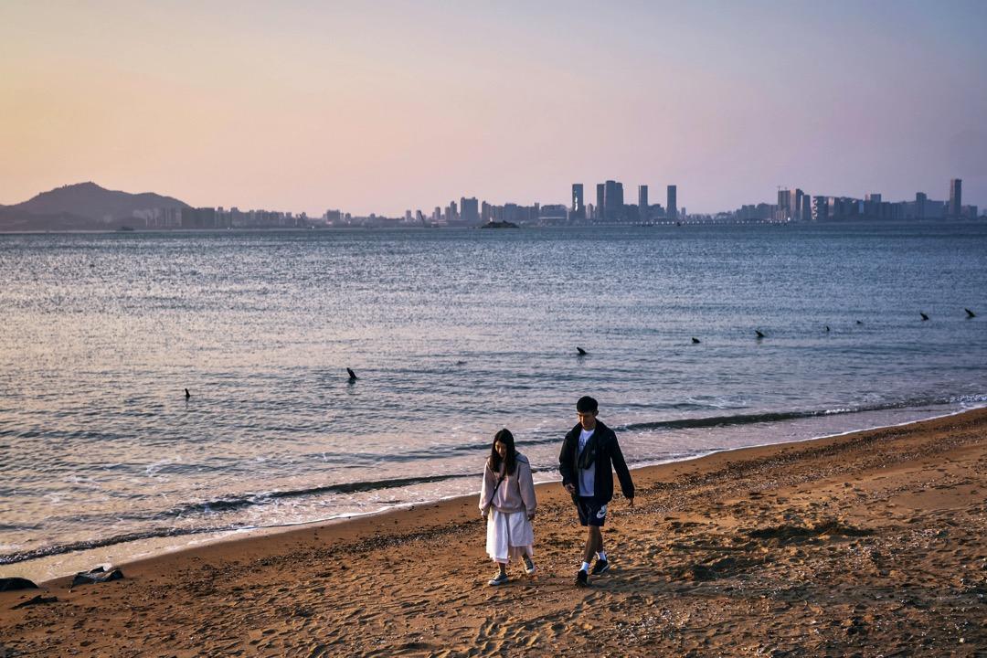 金門眺望廈門的海灘上,一對情侶在散步。