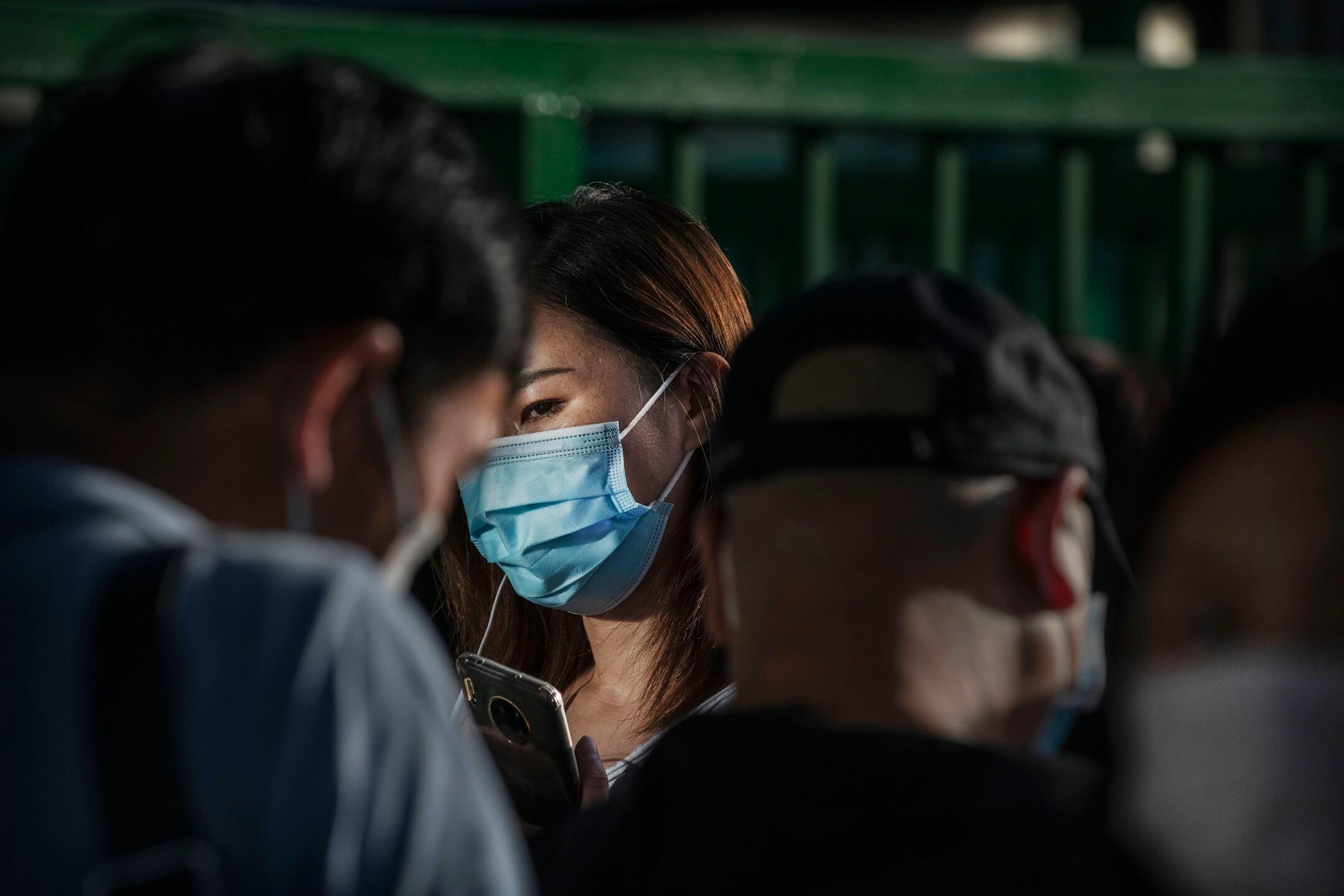 2020年5月,北京,一名戴口罩的女子在巴士站等巴士。 攝:Kevin Frayer/Getty Images