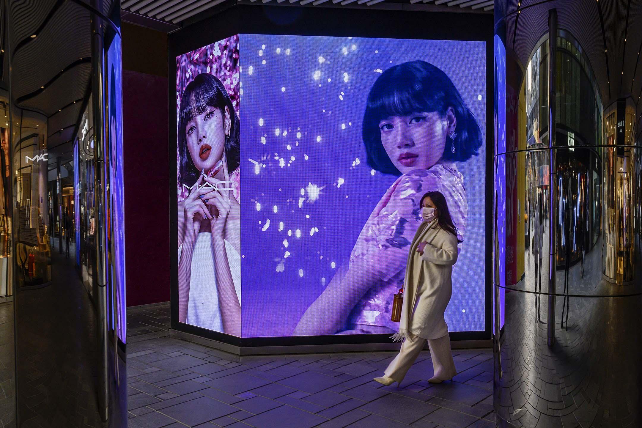 2020年12月9日北京,婦女走過一個化妝品公司的廣告。