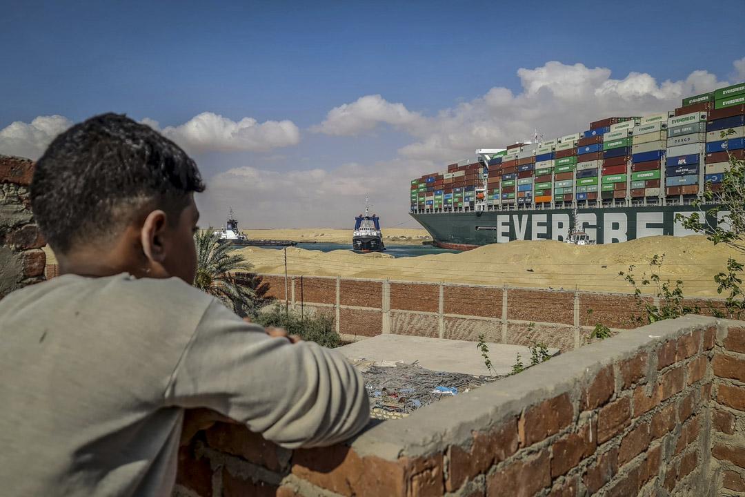 2021年3月26日,一名男孩在遠處觀察在蘇彝士運河擱淺的長榮貨櫃輪船長賜號。 攝:Samuel Mohsen/picture-alliance/dpa/AP Images