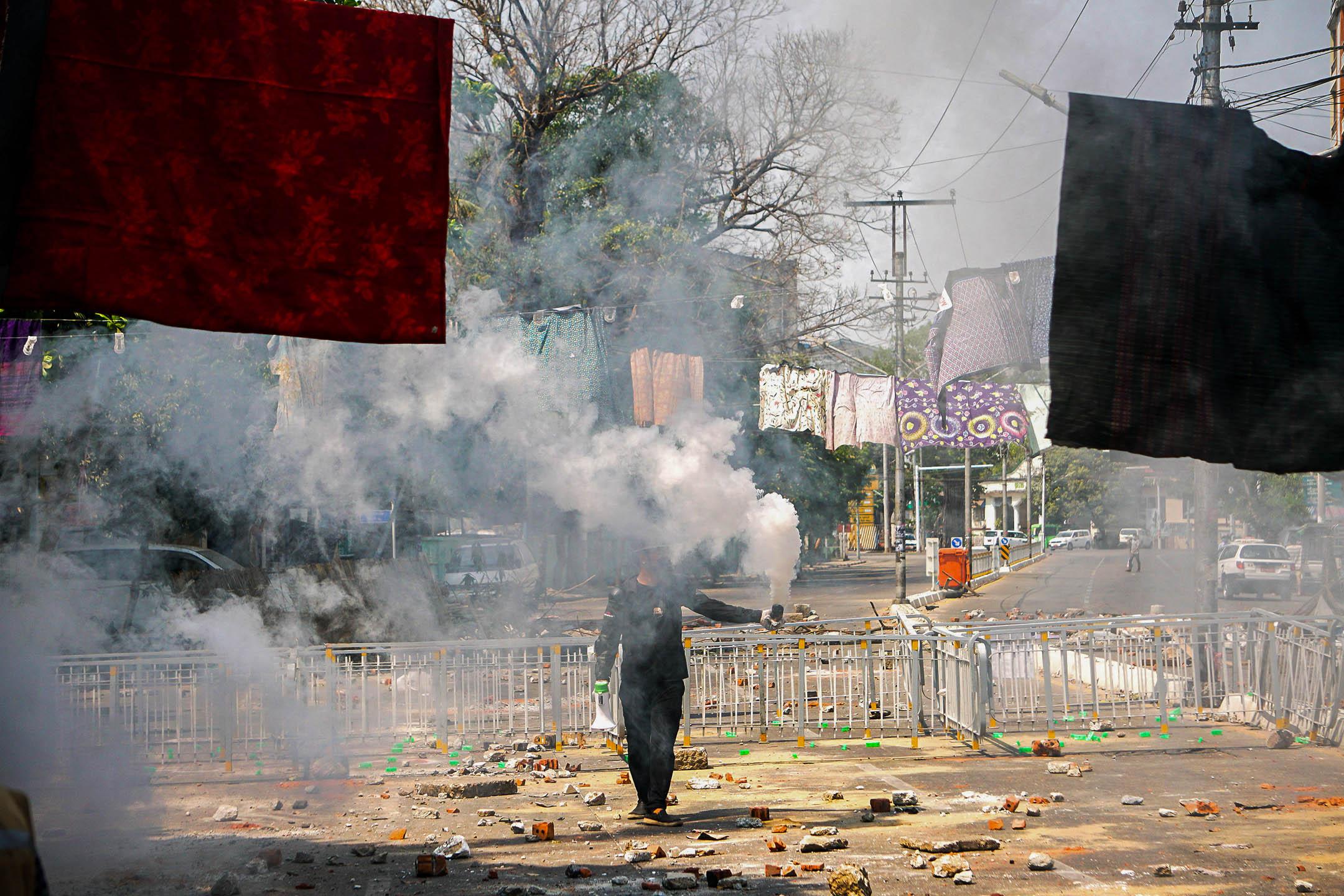 2021年3月9日緬甸仰光,示威者在反政變抗議活動中手持自製的煙霧彈抵抗軍方鎮壓。 攝:Stringer/Anadolu Agency via Getty Images