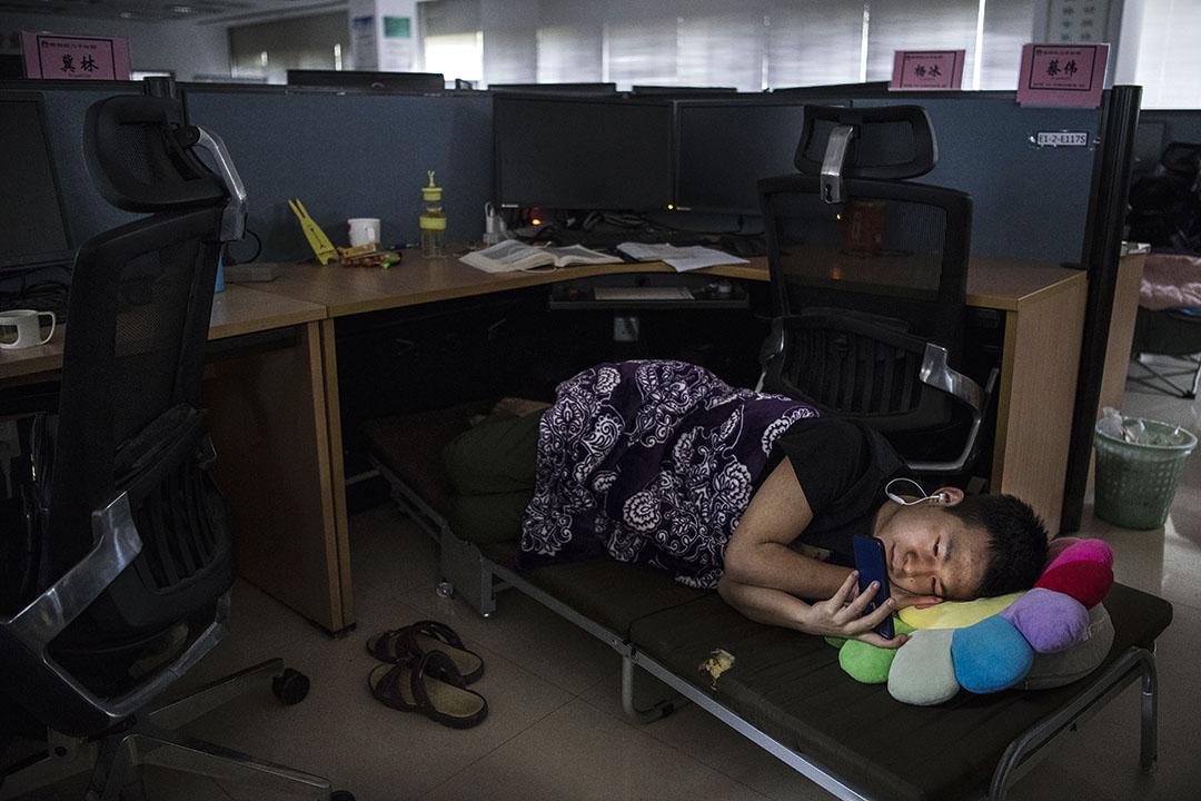 2019年4月12日中國深圳,一名華為員工在午休時間觀看智能手機。