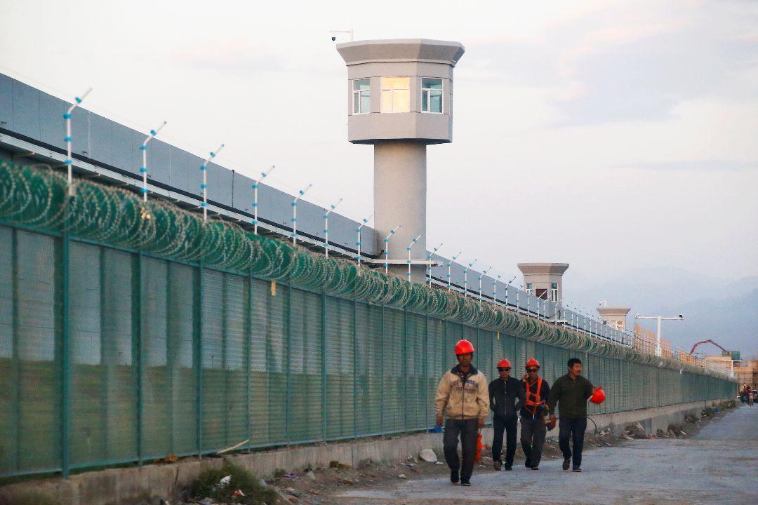 2018年9月4日,中國新疆達阪城,幾名工人走過官方稱為「職業技能教育培訓中心」的圍牆。 攝:Thomas Peter/Reuters