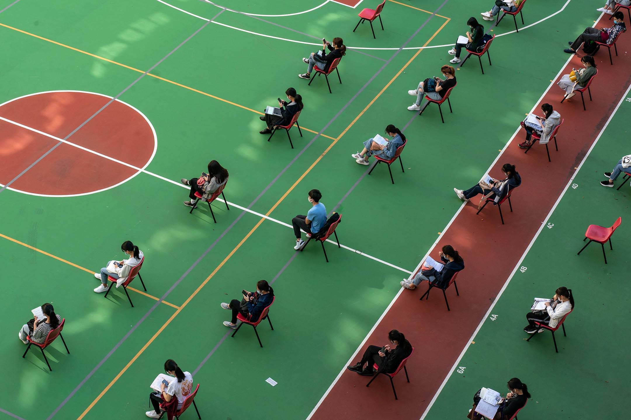 2020年4月29日香港,學生在香港中學文憑試期間,坐在一個操場等待。 攝:Anthony Kwan/Getty Images