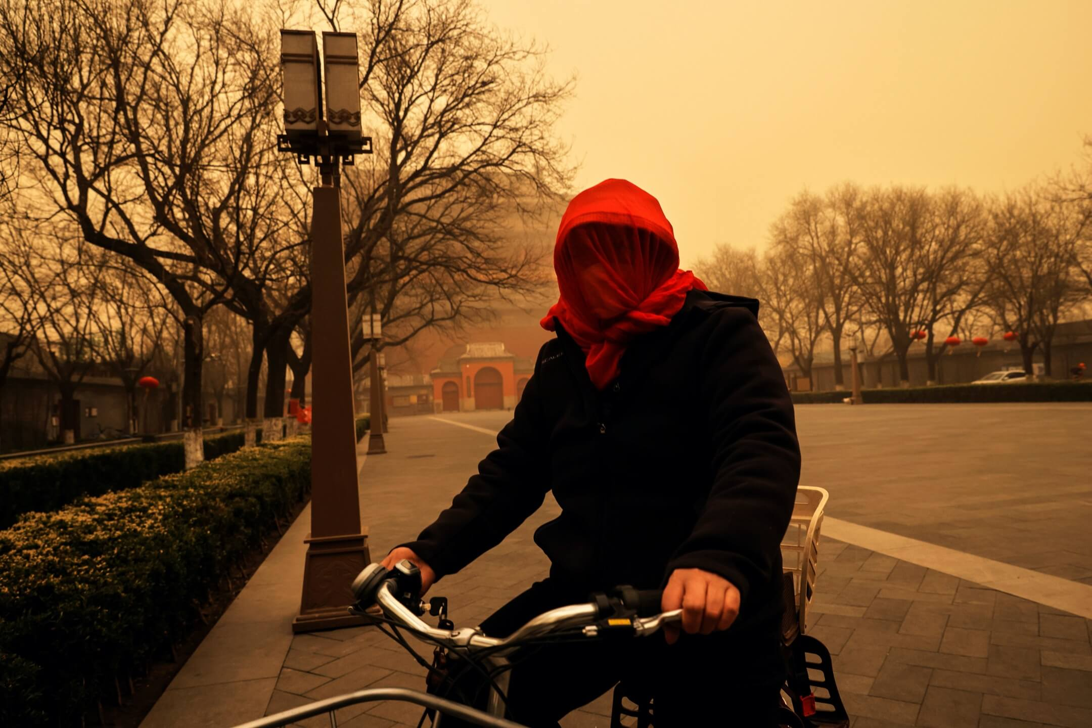 2021年3月15日,北京發生沙塵暴,一名女子騎單車外出時用紗巾蒙頭。 攝:Thomas Peter/Reuters/達志影像