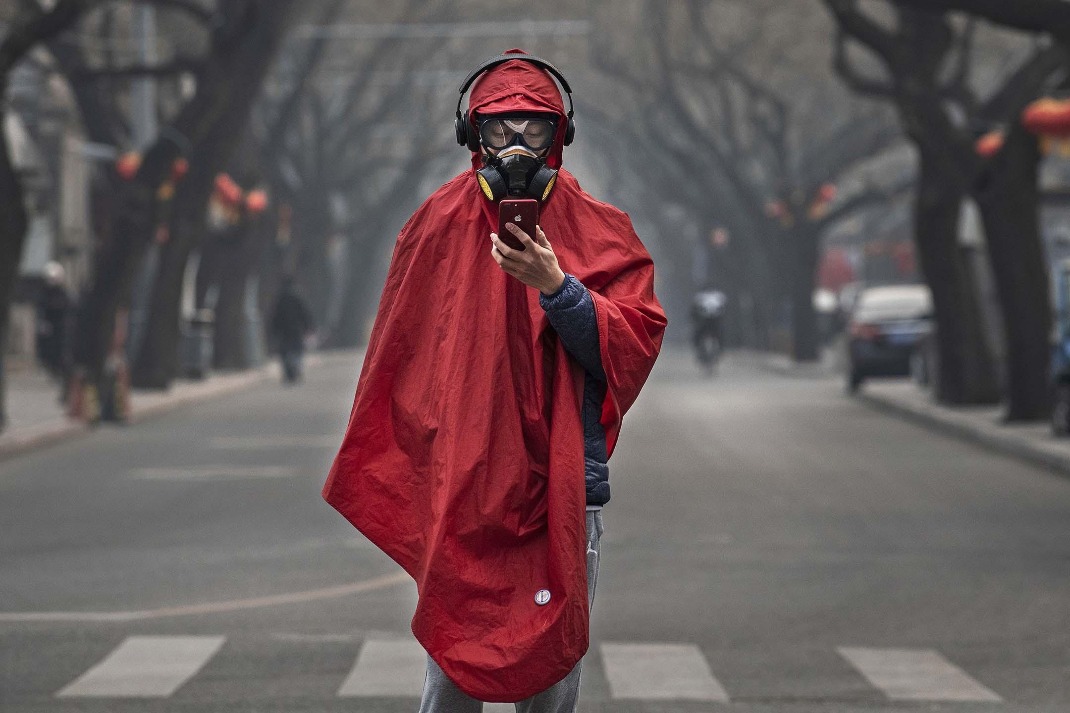 2020年1月26日北京,一名中國男子戴著防護口罩、護目鏡和大衣走在一條空蕩蕩的街道。