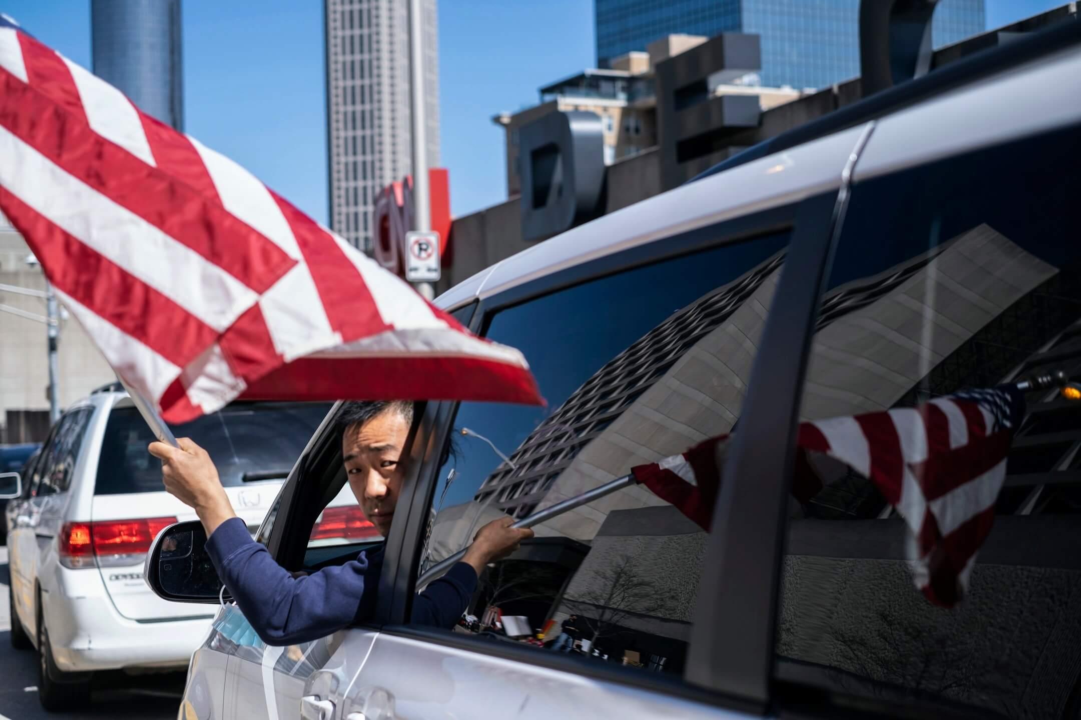 2021年3月20日,美國佐治亞州亞特蘭大市,有「停止仇恨亞裔」集會,一名參加者從車內揮動美國旗。 攝:Ben Gray/AP/達志影像