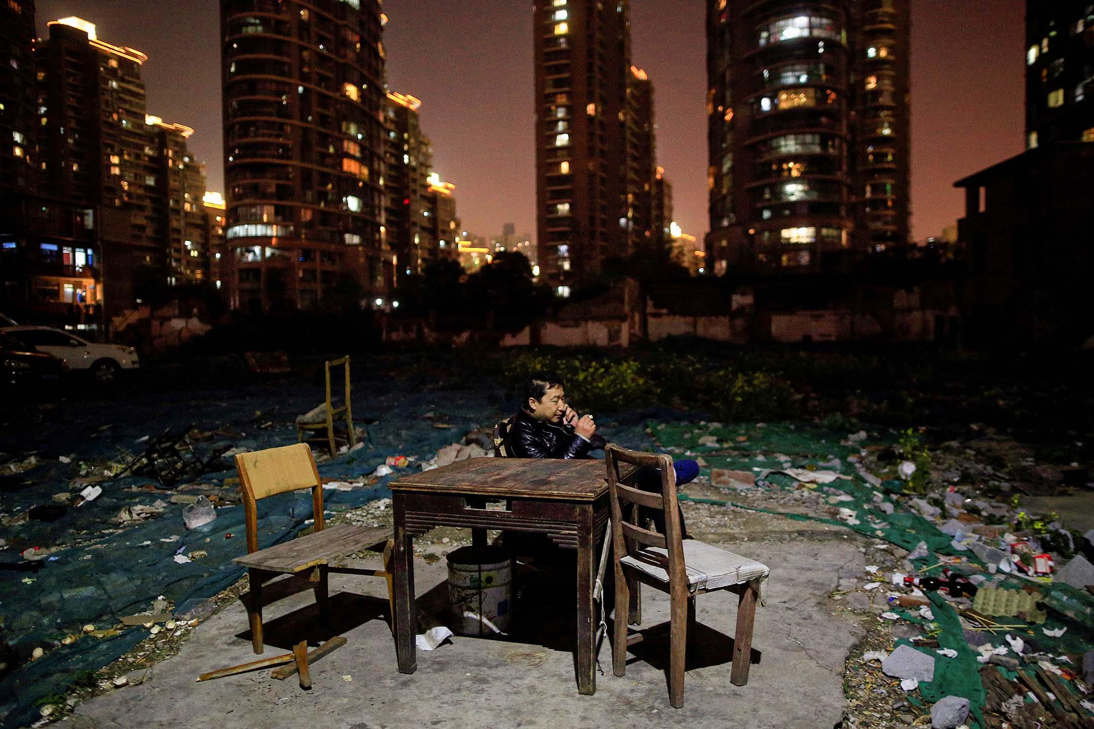 2016年4月1日中國上海,一名男子在社區住宅外使用手機。