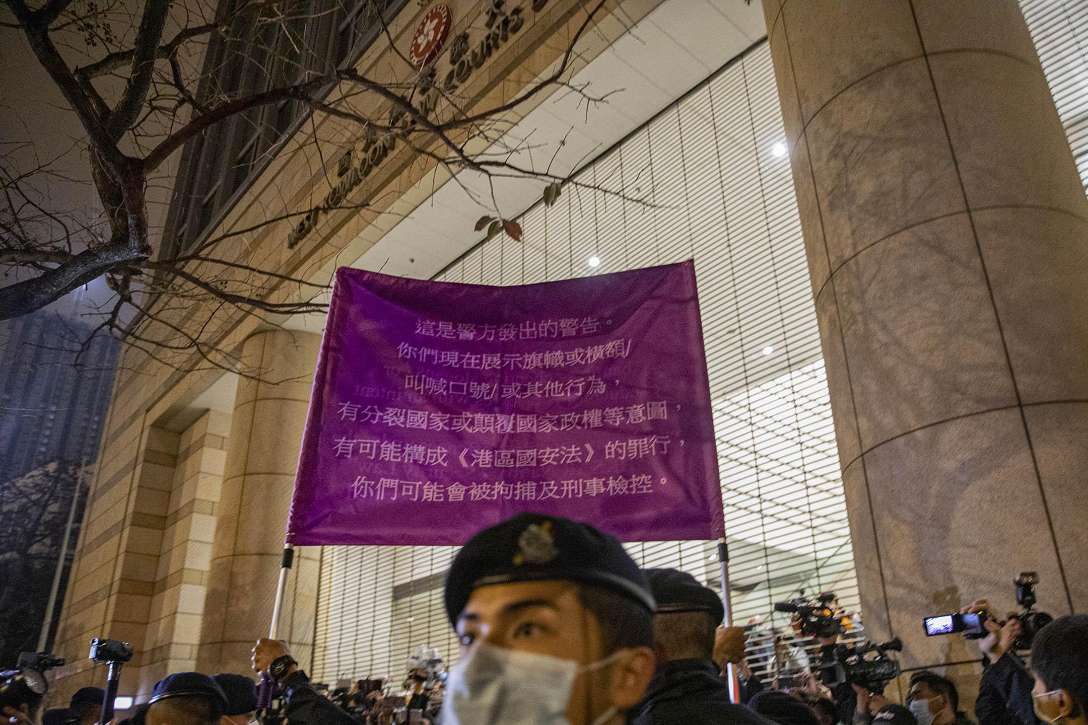 2021年3月4日西九龍裁判法院,市民在法院外聲援各被告,警方出示紫旗驅散。